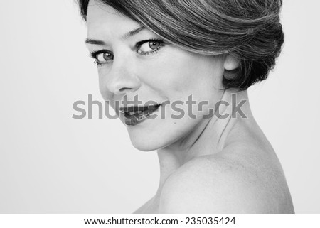 Black and white close up portrait of beautiful middle age woman with bare shoulder - stock photo