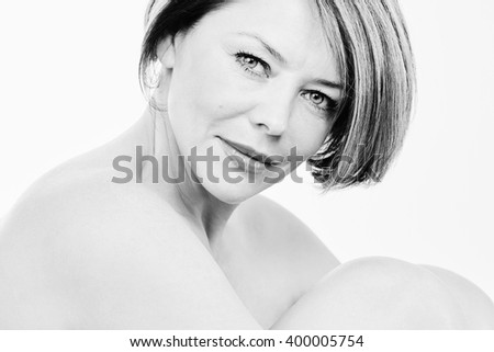 Black and white close up portrait of beautiful middle aged woman with short hair hugging her knees over white background - beauty, skin care or anti aging concept - stock photo