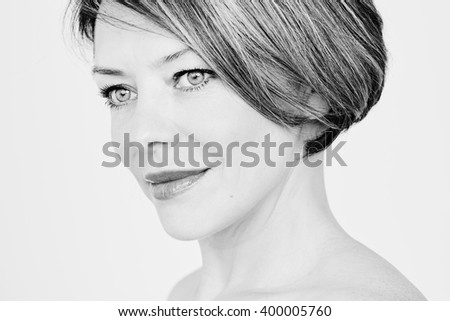 Black and white close up portrait of beautiful middle aged woman with short hair looking aside over white background - beauty, skin care or anti aging concept - stock photo