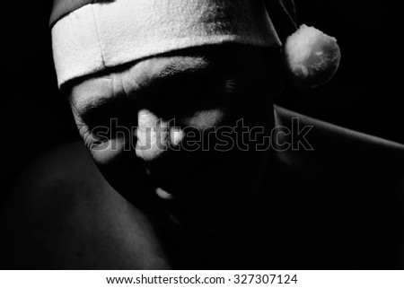 Black and white close up portrait of evil laughing aged man wearing Santa Claus standing against black background - worst Christmas concept