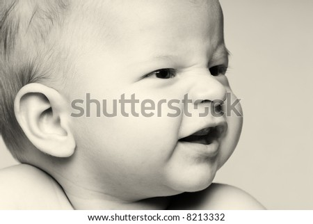 Black and White Close up portrait of little baby looking sideways to the left smiling - stock photo