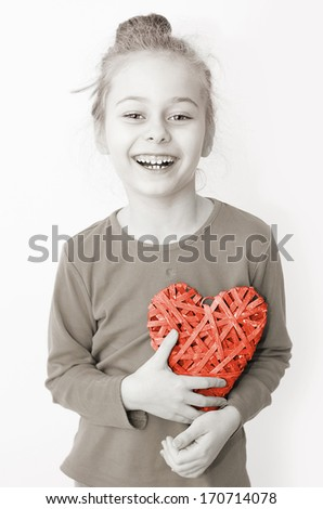 Black and white, close up portrait of smiling five years old caucasian blond child girl holding red heart symbol on a white background. Love, Valentine's Day or happy childhood concept. - stock photo