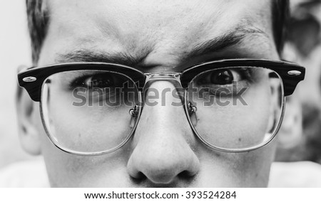 Black and white close-up portrait of the young man in glasses - stock photo