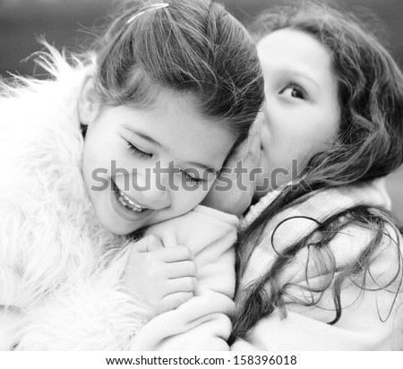 Black and white close up portrait of two young girls children sisters in a park during a cold winter day, with one whispering secrets into the others ear, smiling and laughing outdoors. - stock photo