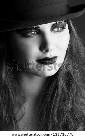 Black and white close up portrait of woman with black make up and hat - stock photo