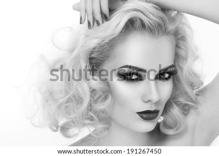 Black and white close-up portrait of young beautiful woman with smoky eyes and blond curly hair - stock photo