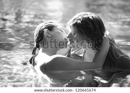 Black and white close up view of a sexy young couple submerged in a swimming pool while dressed, hugging and kissing while on a tropical destination vacation. - stock photo