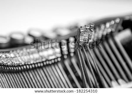 Black and white close-up view of three letters on an old typewriter  - stock photo