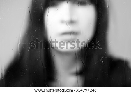 Black and white closeup diffused portrait of brunette girl behind glass concept of melancholy, sadness, loneliness - stock photo