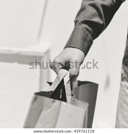 Black and white closeup on person hand holding paper bag with handles, light background - stock photo