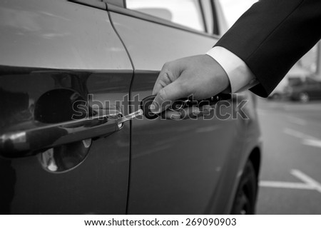Black and white closeup photo of man inserting car key in the hole