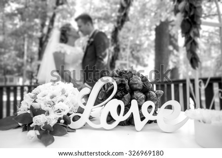 Black and white closeup photo of word Love on table at wedding ceremony