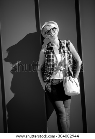 Black and white closeup portrait of stylish hipster girl leaning against wall