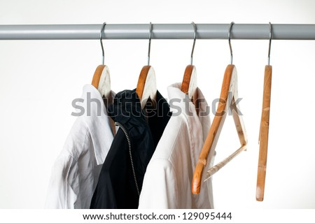 Black and white clothes hanging on a rack in a row, close-up - stock photo