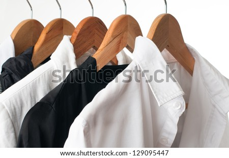 Black and white clothes hanging on a rack in a row, close-up