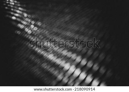 Black and white coarse bokeh on the metallic grill, out of focus - stock photo
