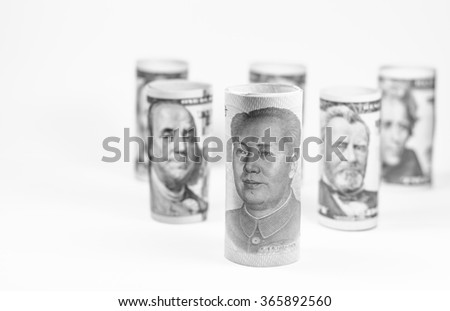 Black and white color with Chinese currency and American dollars roll,Focus on Chinese currency - stock photo