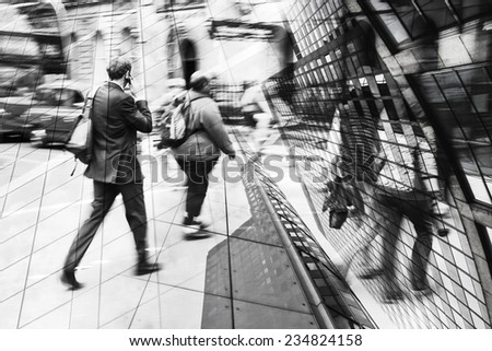 black and white compositing image of a phoning businessman in the city overlaid with a picture of skyscrapers - stock photo