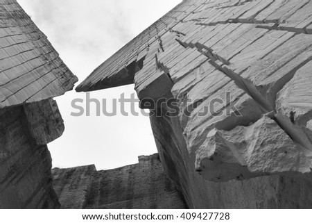 Black and white composition of the ancient entrance to the main pit of the Lithica quarry in Menorca, a sandstone block production place since prehistory. - stock photo