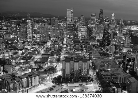 Black and white composition of the city of Seattle at night, Washington, with neon lights illuminating the big apartment buildings and offices downtown - stock photo