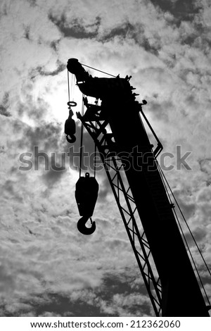 Black and white crane truck is working on sky background - stock photo