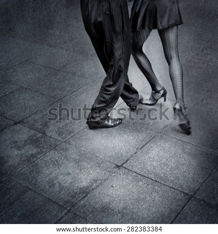 Black and white detail image of a couple dancing tango on the street in Argentina.
