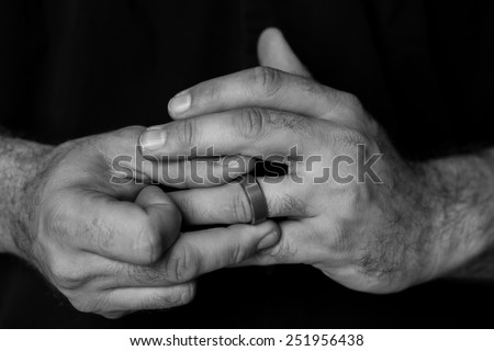 Black and white detail of a man's hands fidgeting with a wedding ring