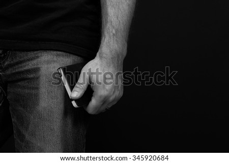 Black and white detail of a man wearing jeans and a t shirt holding a pocket knife at his side