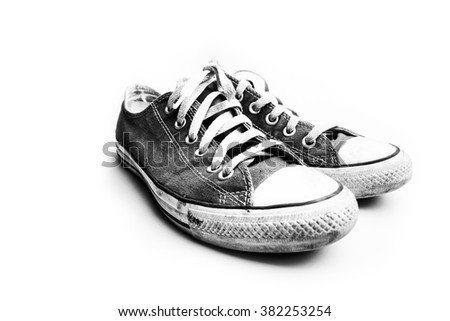 Black and white dirty shoes isolated on white background