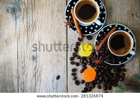 Black and white dots cup of coffee on the old wooden table with coffee beans, cinnamon sticks and anise star - stock photo