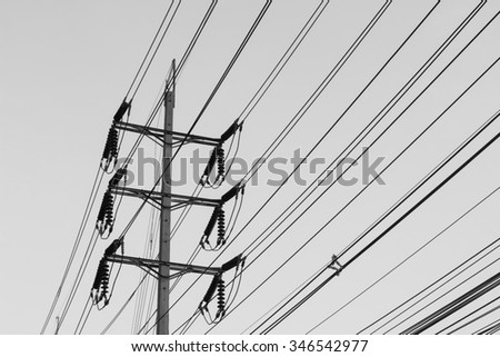 Black and White electric pole on bright sky.
