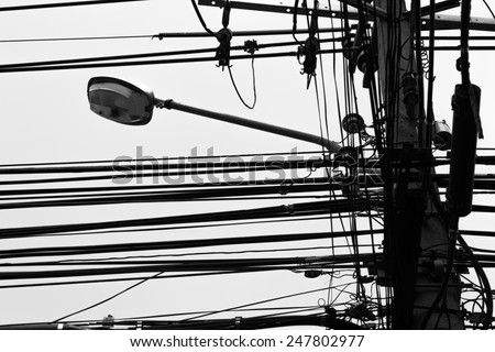 Black and white electricity post and untidy wire in Thailand
