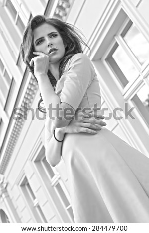 Black and white fashion portrait of a young pretty girl with old building in background , she is looking away - stock photo