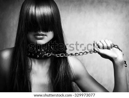 Black and white fashion portrait of young beautiful female model. Glamour woman with long black hair and sexy hairstyle. Lady with leather collar with studs on a metal chain in hand