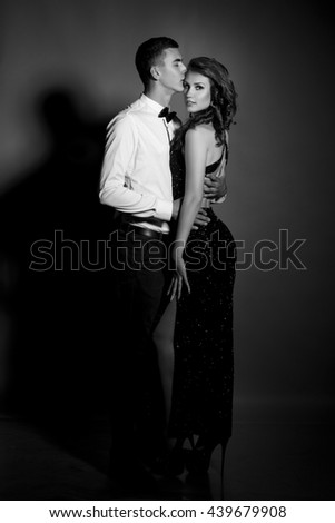 Black and white fashion studio photo of beautiful couple, Fashionable loving man woman in elegant clothes, embracing each other, soft grain filter, series
