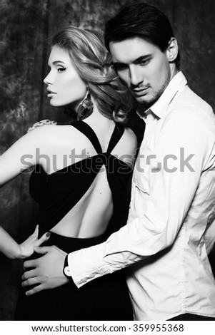 black and white fashion studio photo of beautiful couple, wears elegant clothes, embracing each other