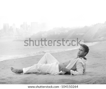Black and white fine art portrait of a sexy young man in casual clothing lying on the beach - stock photo