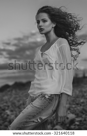 Black and white fine art portrait of a young woman on a beach