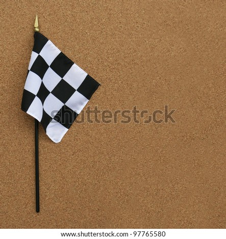 Black and White Finish Line Checkered Flag isolated on cork board background with room for your text - stock photo