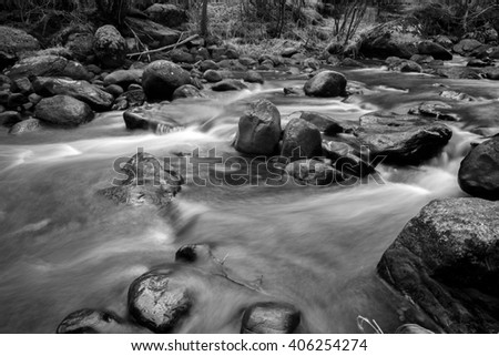 Black and white forest river going through rocks and boulders. - stock photo