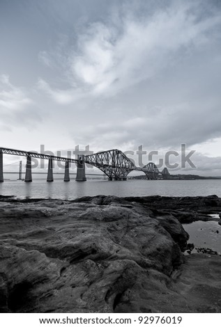 Black and White Forth Rail Bridge with foreground rocks in Scotland - stock photo