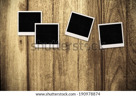 Black and white frames on vintage wooden background.