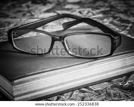 black and white glasses and book
