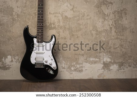 Black and white guitar on the floor near the concrete wall - stock photo