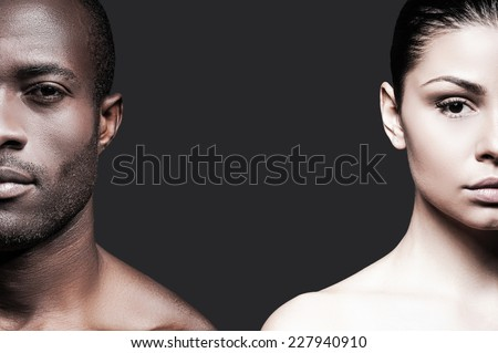 Black and white. Half faces of shirtless African man and Caucasian woman looking at camera while standing against grey background  - stock photo