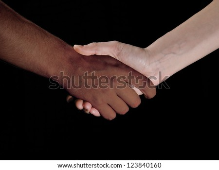 Black and white hand shaking together in friendship or partnership - stock photo