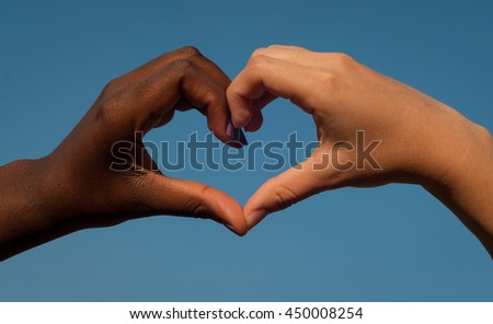 Black and white hands in heart shape, interracial friendship - stock photo