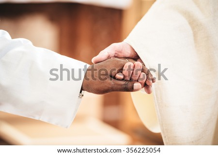 Black and white hands of two priest men