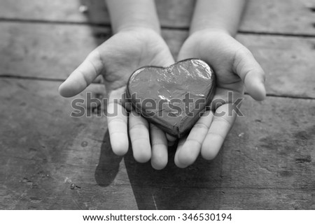 Black and white heart in child's hands - stock photo