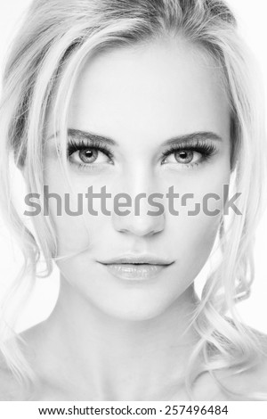 Black and white hi-key portrait of young beautiful blonde girl with extended eyelashes - stock photo